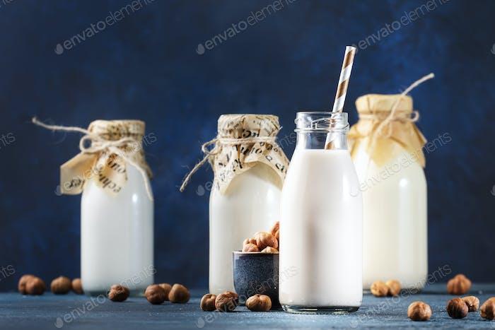 Vegan Hazelnut nut milk in bottles, closeup, blue table