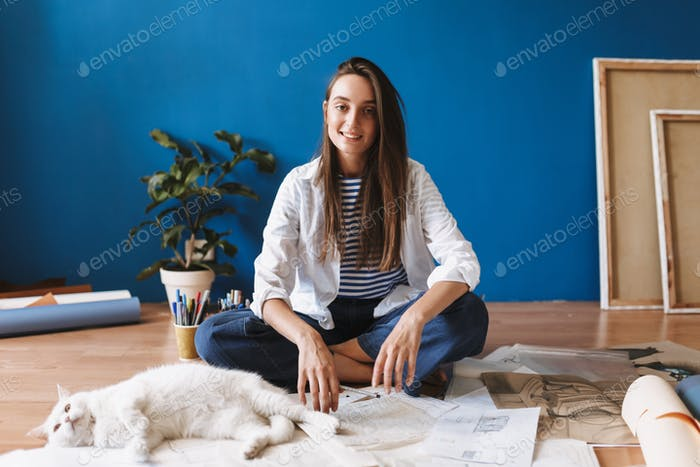 Beautiful smiling girl sitting on floor with drawings happily lo