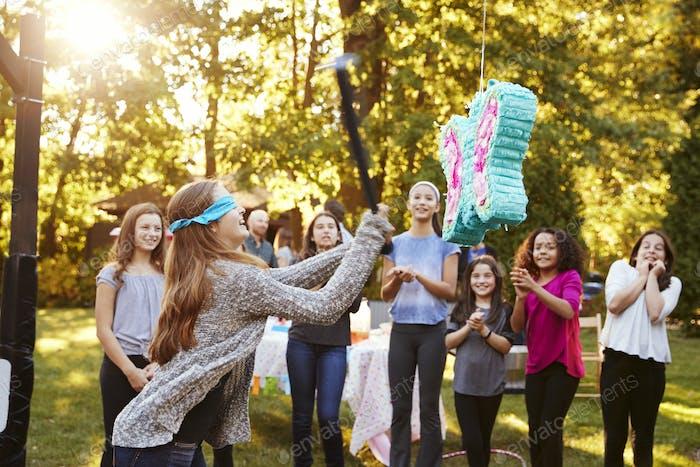Freunde sehen Teenager-Mädchen schlagen eine piata auf ihrem Geburtstag