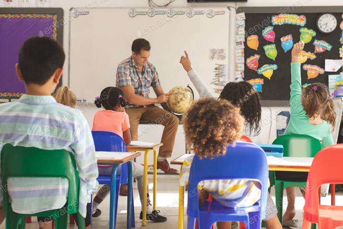 schoolteacher learning at his pupils the earth globe in classroom at school with school kids