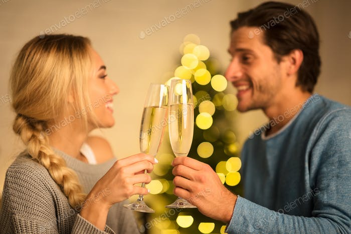 Happy couple with glasses of champagne celebrating Christmas
