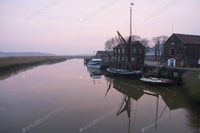 Sailing boats moored at harbour wall, reflected on the surface of a calm canal at twilight.