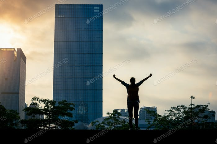 Woman open arms in the sunrise city