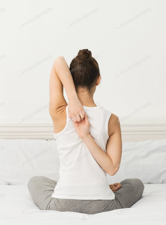 Young woman practicing yoga in Cow Face Pose, crop