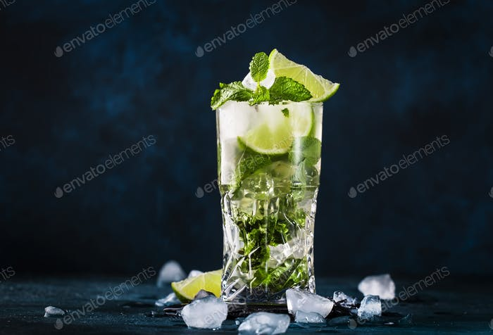 Mojito cocktail or mocktail with lime, mint, and ice in glass on blue background