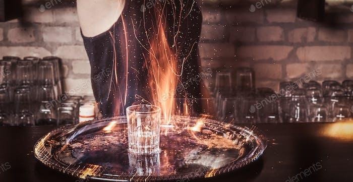 Бородатый бармен наливает корицу в коктейль