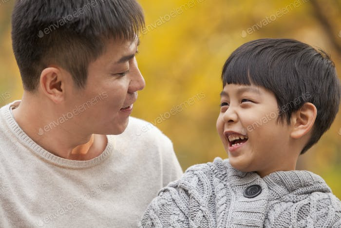 Father and son laughing in the park in autumn, close-up