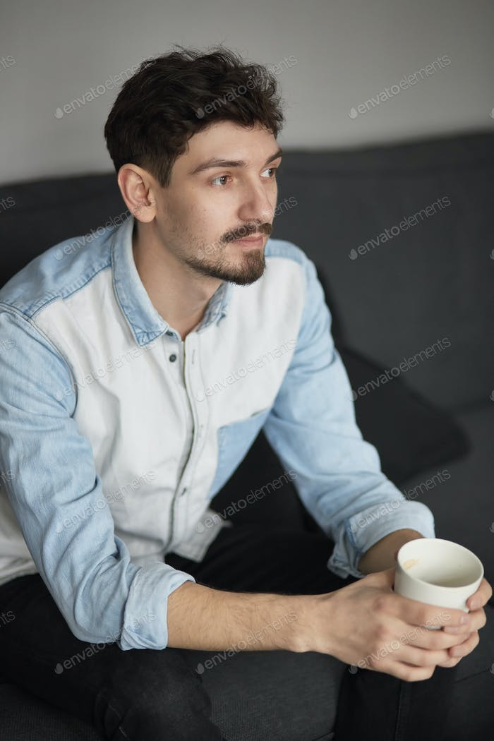 Freelancer resting with a cup of coffee on a couch while thinkin