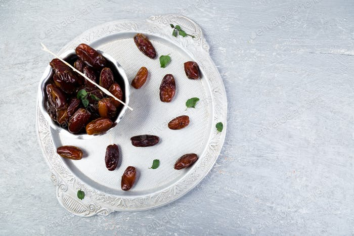 Dry fruit dates on silver tray. Copy space. Top view.