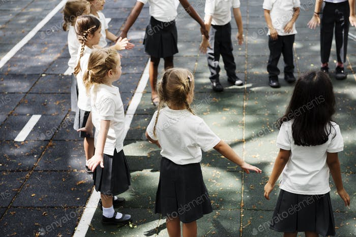 Group of diverse kindergarten students standing holding hands to