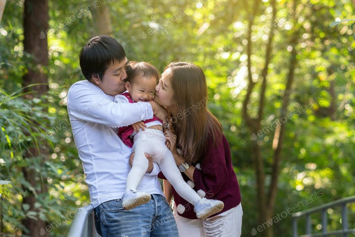 Asian Mother with Father carrying and kissing daughter in the forest, Family