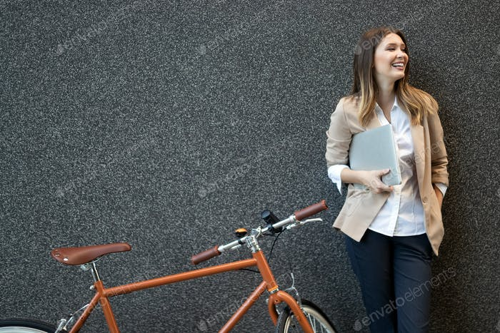 Business woman with bicycle to work on urban street in city. Transport and healthy lifestyle concept