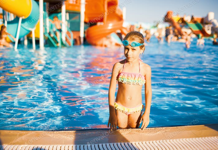 Funny girl in glasses for swimming stands in a pool with clear transparent water