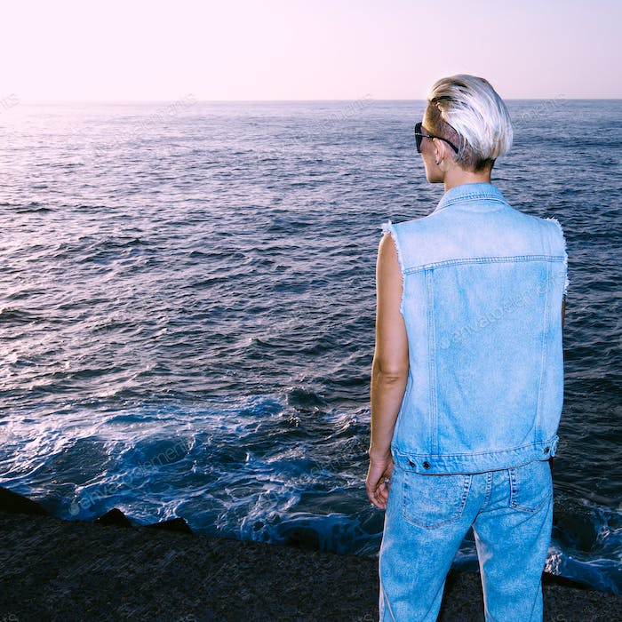 Model in stylish denim outfit sea background sunset