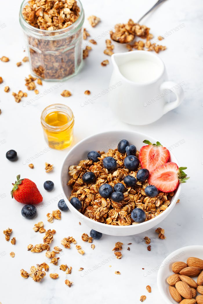 Healthy breakfast Fresh granola, muesli in bowl with milk and berries