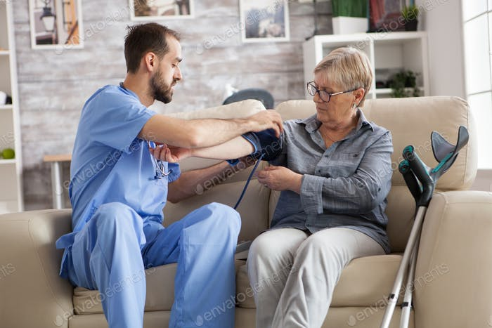 Male nurse with old woman on couch in nursing home