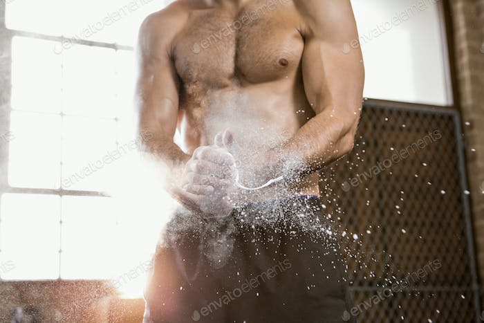Midsection of a muscular man applying chalk powder at the gym