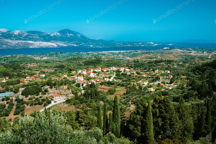 View of idyllic valley town with red roofs on mediterranean island. Olive groves, cypresses and blue