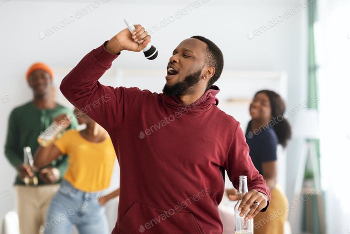 Positive black guy with bottle of beer singing karaoke