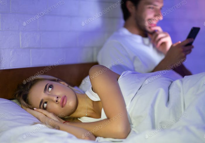 Man Texting On Mobile Phone Lying In Bed With Wife