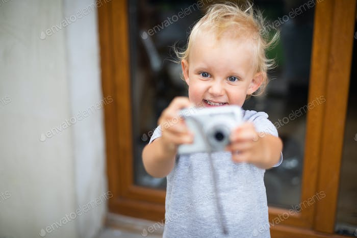 Cute little child boy playing with digital camera taking a photos