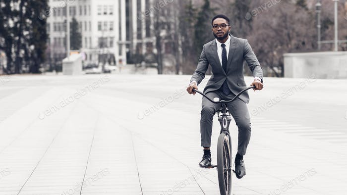 Businessman riding on bicycle to office, free space