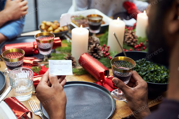 Group Of Friends Sitting Around Table At Home For Christmas Dinner Reading Jokes From Crackers