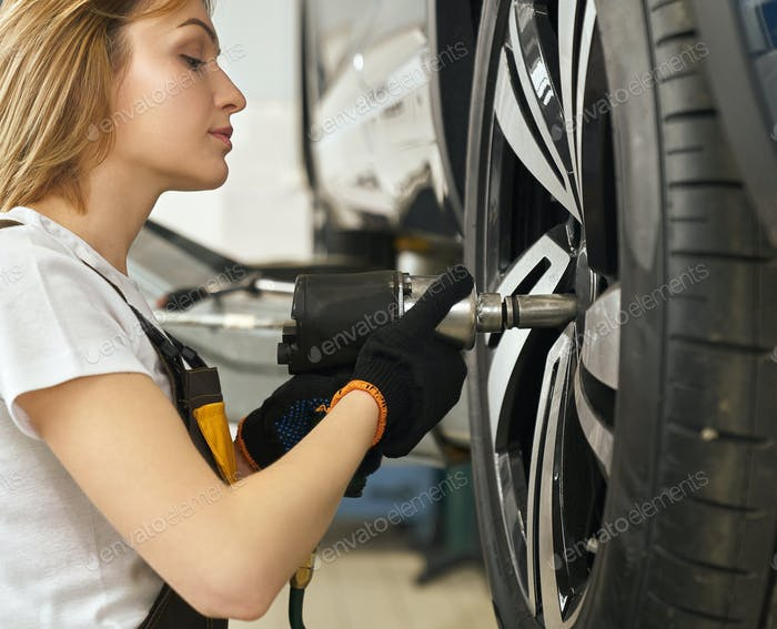 Side view of female mechanic changing tire of auto