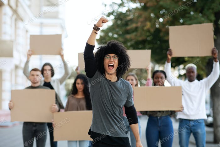 Guy leading international group of students strikers with blank placards