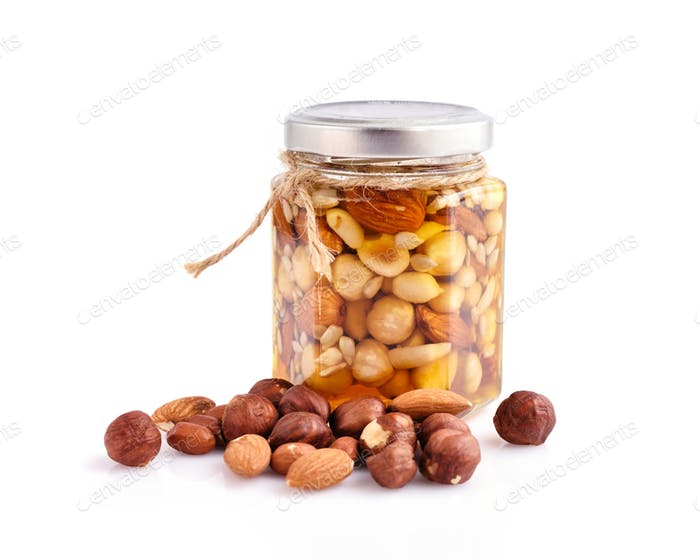 Healthy mix of natural honey with different nuts in a jar on whi