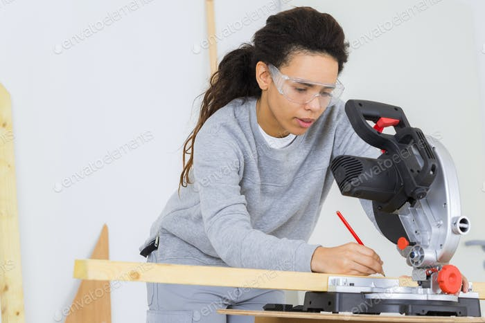 woman sanding a pieces of wood by electric sander diy
