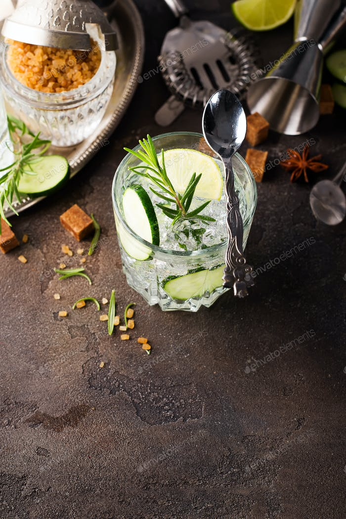 Transparent refreshing drink with cucumber, lemon and rosemary