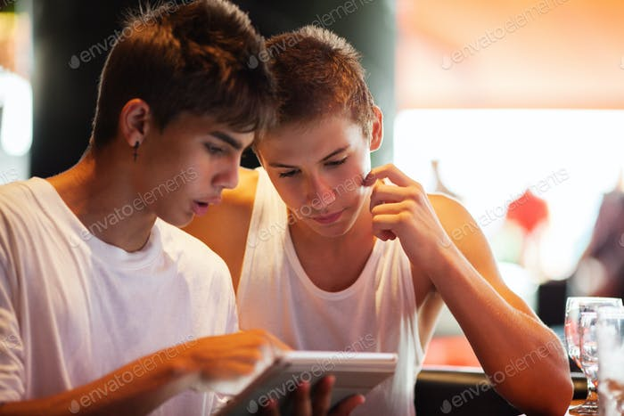 Young men searching on the internet with pad in cafe