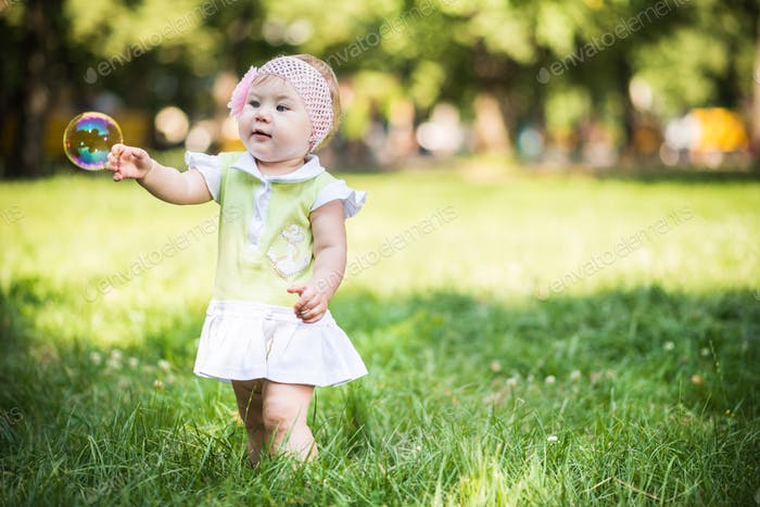 Small baby girl walking on grass and trying to catch bubbles