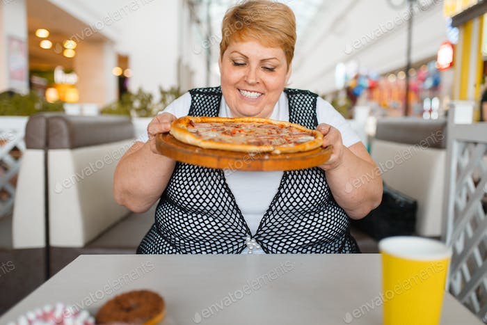 Fat woman eating pizza, unhealthy food