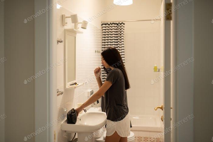 Young female brushing teeth in bathroom