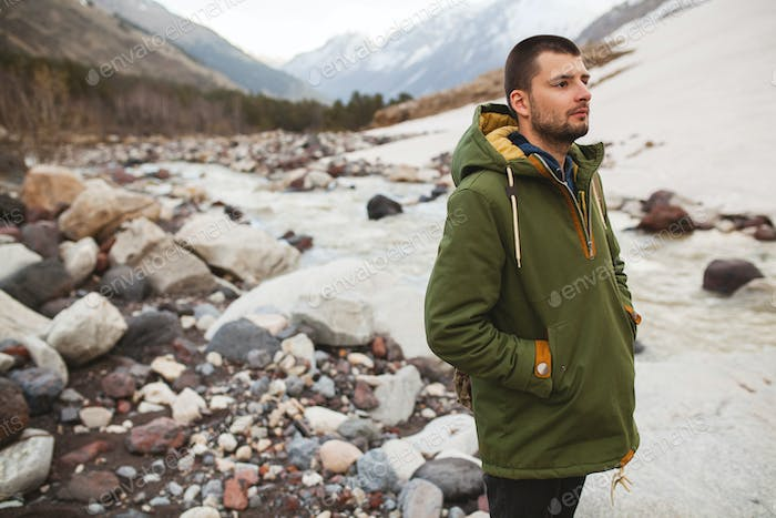 young hipster man hiking in mountains
