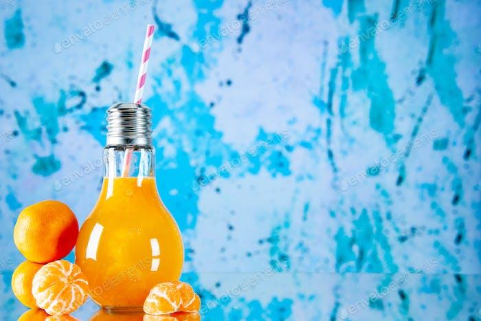 Draufsicht auf köstlichen frischen Fruchtsaft, serviert mit Tube und geschälten und ungeschälten Mandarinen auf der