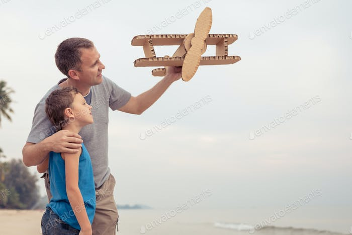 Father and son playing with cardboard toy airplane