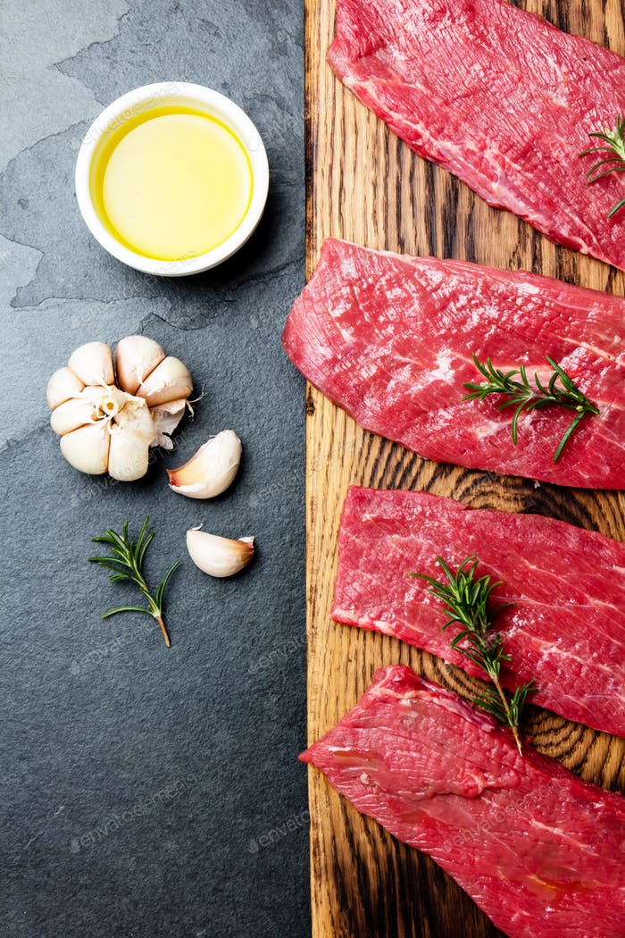 Fresh raw meat beef steaks. Beef tenderloin on wooden board, spices, herbs, oil