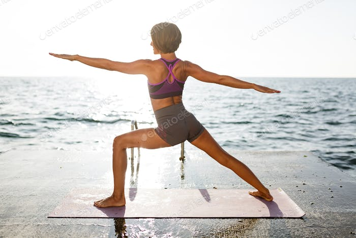 Young lady in sporty top and shorts practicing yoga with amazing sea view on background