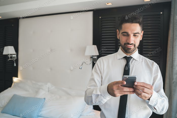 Businessman using his mobile phone at the hotel room.