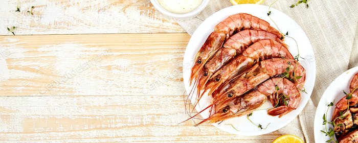 Banner with Grilled big tiger shrimps prawns on white plate