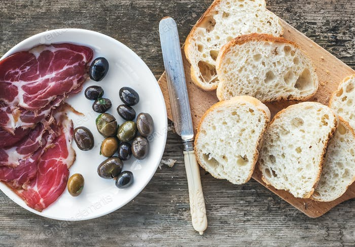 Smoked meat or prosciutto and olives on a white plate, vintage knife, baguette slices