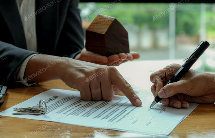 Seller hand point the customer use pen to sign the contract with home model on seller hand.