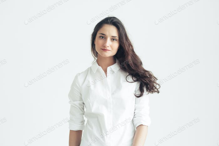 Brunette female in white shirt ower white wall. Attractive female natural casual