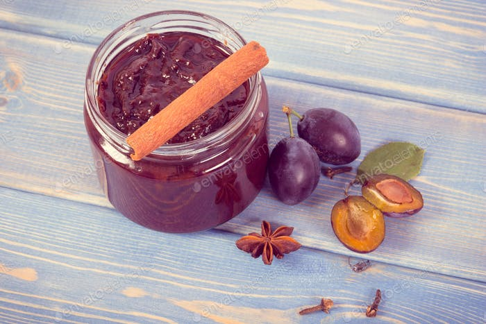 Vintage photo, Fresh plum marmalade in jar, ripe fruits and spices on boards, healthy sweet dessert