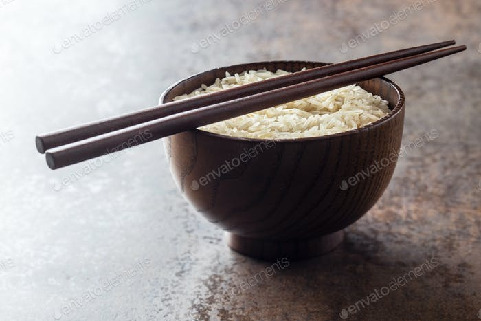 Uncooked indian long rice in bowl and chopsticks.