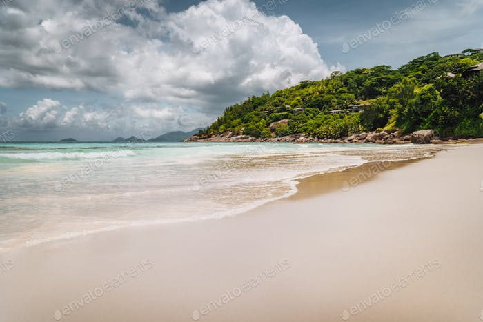 Beautiful long sandy Petite Anse beach at Mahe Island, Seychelles. Huge rainy clouds in sky. Holiday