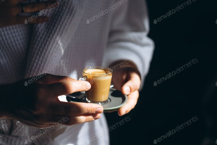 A man in a bathrobe is holding a small mug of coffee